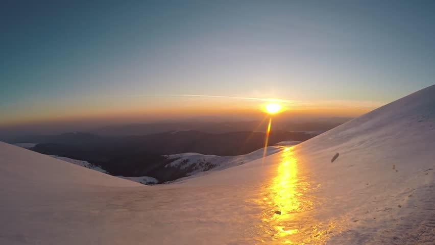 Climbimg on the snow mountain hills. Sunset on the mountains. Winter mountain view. Going up the hill. Clear blue sky. Top of the mountain. Sunset in winter.    Shutterstock HD Video #1027547456