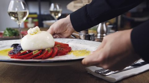In the restaurant, food and wine are on the table. On the table is a vegetable salad and burrata cheese with tomatoes. Burrata cheese stands on a wooden table in a cafe.