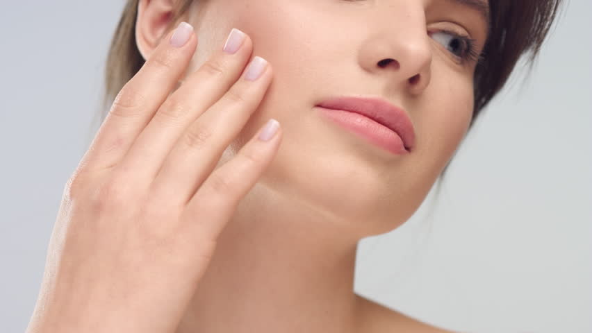 Close-up beauty portrait of young woman with smooth healthy skin, she gently touches her face with her fingers on light grey background and smiles | Skincare concept | Shutterstock HD Video #1027606286