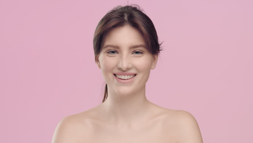 Close-up beauty portrait of young beautiful brown-haired Caucasian woman with smooth healthy skin and nude make-up turns to camera and smiles in studio at the light pink background | Skincare conce