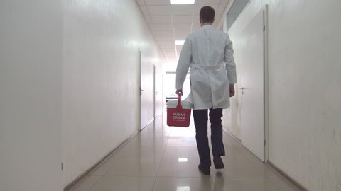 Doctor with red organ trafficking container going along the corridor towards the exit from the hospital.
