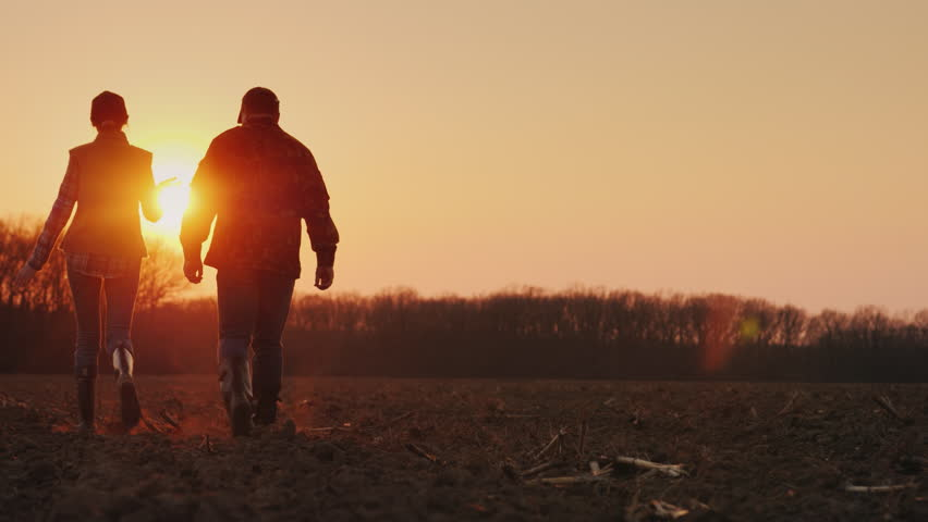 Silhouettes of two farmers walking across the field towards the rising sun