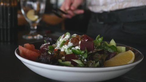 Pouring lemon juice and olive oil to healthy green salad of lettuce, arugula, marinated beat, sliced fresh tomatoes, cucumber, raisins and dry mulberry