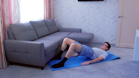 Funny nerd man in glasses is doing buttock bridge exercise on mat to strengthen the muscles of the legs at home. Sport humor concept.