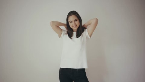 Beautiful young slim brunette girl posing in front of the camera in white blank t-shirt and black jeans, white isolated background, showing the back and front for the mock-up, smiling happily