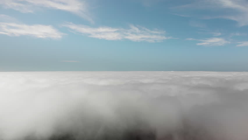 Aerial shot. Beautiful flight above the clouds over the volcanic valley. Tenerife, Canary Islands, Spain. The concept of dreaming, flying, elevation and flying above the clouds.