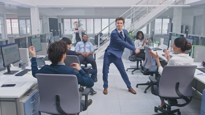 Young Happy Business Manager Wearing a Suit and Tie Dancing in the Office. Colleagues are Cheering. Diverse and Motivated Business People Work on Computers in Modern Open Office. #1027712576