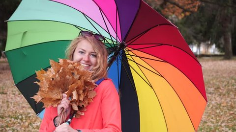 Happy longhaired blonde woman with a large colourful umbrella in a red coat in the autumn park turns around and smiles at the camera with yellow maple leaves in her hand.