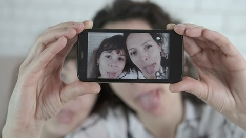 Funny selfie. A woman with a child is grimacing. Mother and daughter are photographed on a smartphone.