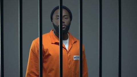 Aggressive black prisoner showing medium finger, dangerous criminal imprisoned