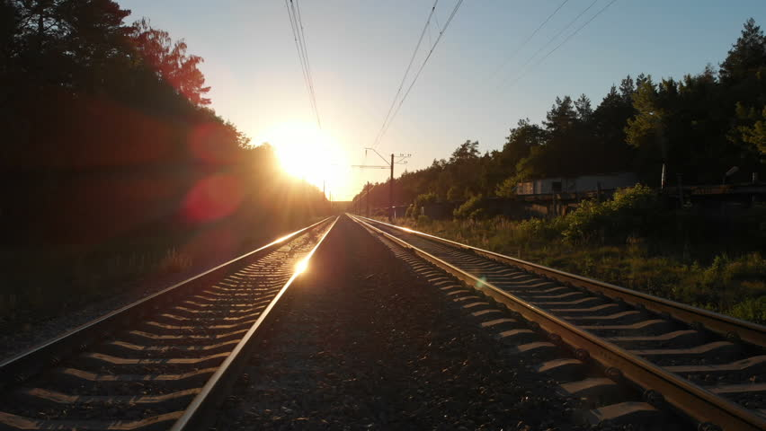 Beautiful railroad stretching through a forest at sunset in 4k | Shutterstock HD Video #1027774016