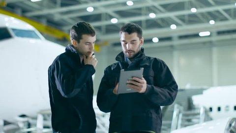 Team of Aircraft Mechanics and Engineers Waking Through Airplane Maintenance, Design and Development Facility. Professionals Consulting Digital Tablet Computer, Talking and Smiling