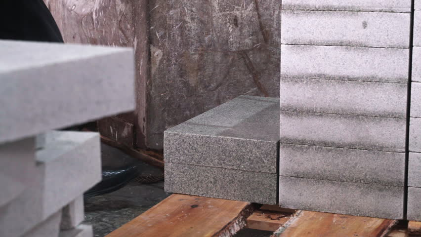 The worker puts granite slab at a warehouse of stone products  | Shutterstock HD Video #1027781276