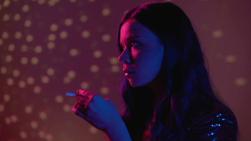 Serious young woman smoking cigarette at nightclub party, unhealthy habit #1027802216