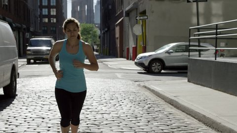 Woman Jogging on Cobblestone Street in BK with Brooklyn Bridge in Background - Female Athlete Running - Runner in Slow Motion 4K - Jogger Training in New York City - NYC, USA