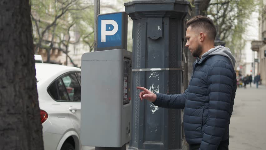 Close up shot of a man inserting a parking lot ticket at an automated pay machine. Cash Automated machines have taken the place of human staffed parking lot attendants. | Shutterstock HD Video #1027804346