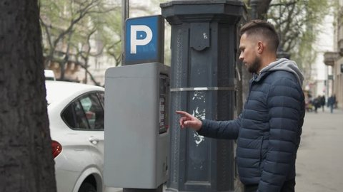 Close up shot of a man inserting a parking lot ticket at an automated pay machine. Cash Automated machines have taken the place of human staffed parking lot attendants.