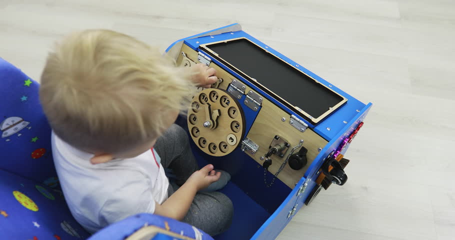 New educational toy Montessori. A little boy is playing fun in the car. The development of babies. Fine motor skills. Sensory sensitivity.   Shutterstock HD Video #1027815896