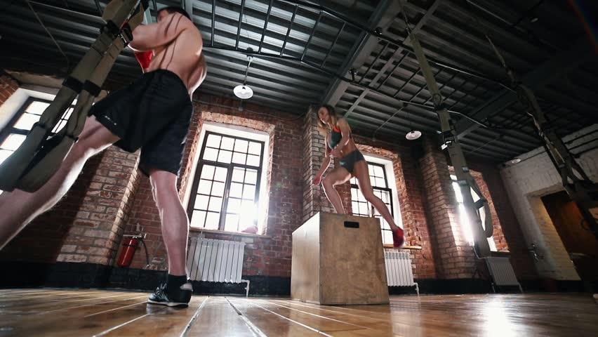 An athlete people on training. A woman jumping on the box while a man punching the punching bag