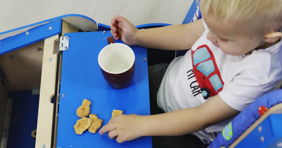 A little boy sits in his busycar and eats cookies and drinks tea.  Educational toy Montessori. Fine motor skills. Sensory sensitivity.   Shutterstock HD Video #1027889996