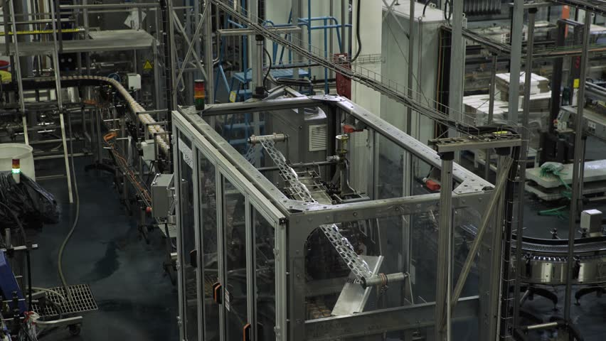 Machine putting six pack rings on aluminium cans in large packaging factory