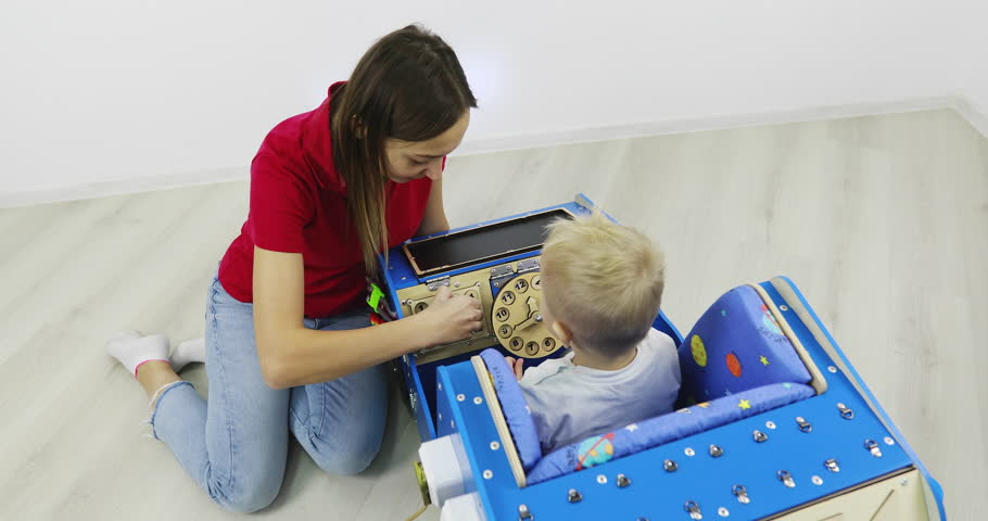 Busy Car. Mother with a small child plays with a wooden car toy. A special toy car model with many functions for the development of fine motor skills.   Shutterstock HD Video #1027920836