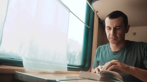 man reading a book in a train long journey. railroad travel concept coach train journey. view beautiful from the window of a moving train railway Russia winter. interior inside lifestyle train
