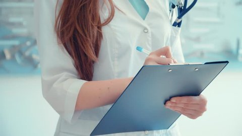 Female doctor holding clipboard with case-history and writing conclusion of treatment on background with surgical instruments. Medical education concept.