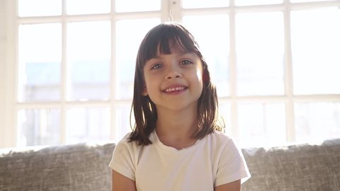 Cute small girl blogger talking to camera recording vlog at home, happy little vlogger waving hand looking at webcam kid child make video call on communicate online sit on sofa at home