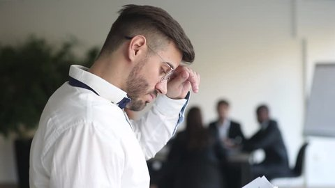Anxious stressed conference speaker presenter read papers financial report afraid of public speaking at presentation, nervous concerned businessman feeling fear panic worried about speech performance