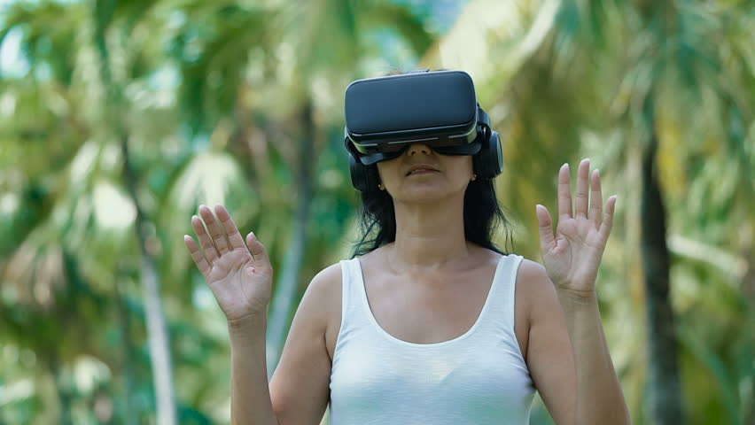 Woman with virtual reality goggles outdoors. Green trees background on sunny day. Technology, virtual reality, entertainment and people concept