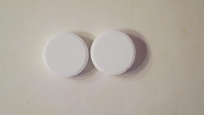 Large round tablets on a light surface. | Shutterstock HD Video #1028047226