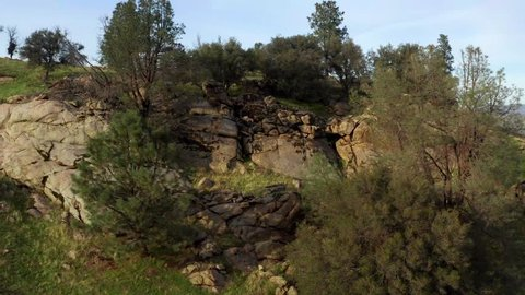 Aerial Rising Reveal of Vast Foothill Mountains Beyond Rocky Outcrop, California