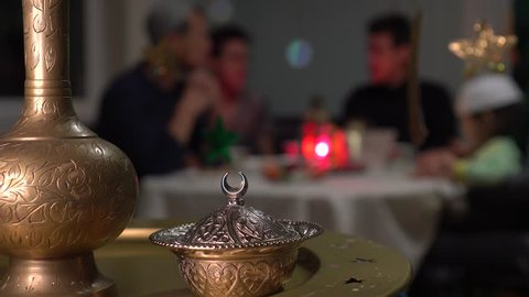 Eid Mubarak. Muslim people eating food during Iftar at home. Traditional evening meal for Ramadan. The Islamic Halal Eating and Drinking