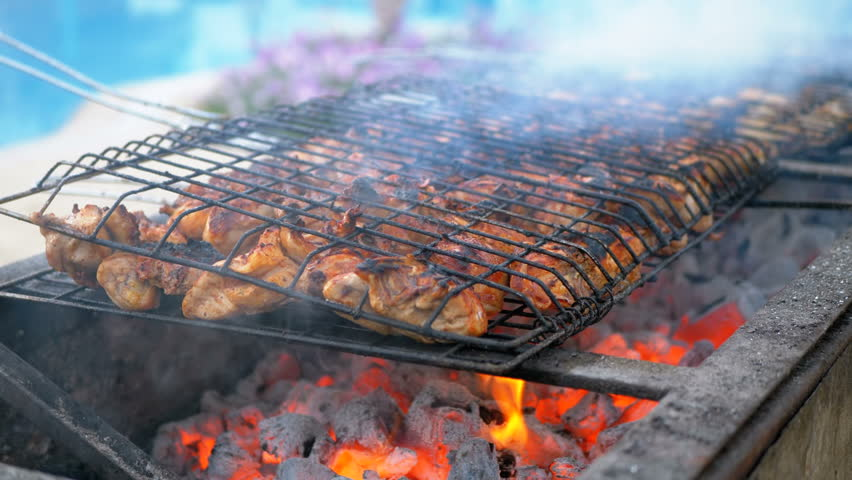 Chicken Barbecue are Cooked on a Large Grill by a Cook at the Hotel by the Pool with Blue Water. Egypt. Cooking kebabs on the grid for a large number of people. Barbecue by the pool with sun beds and | Shutterstock HD Video #1028094176