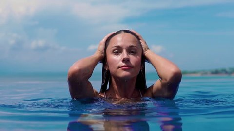 The beautiful girl comes up from pool and from it water flows down. Close up. Female Enjoying Summer Travel In Swimming Pool At Luxury Resort