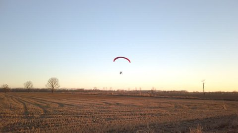 Paragliding with parachute flies into the sky and then the trike lands in  the agricultural fields below at sunset