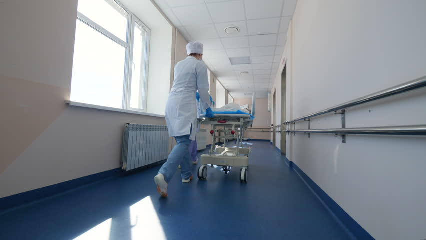 Doctors are riding an ambulance cart through the corridor #1028120816