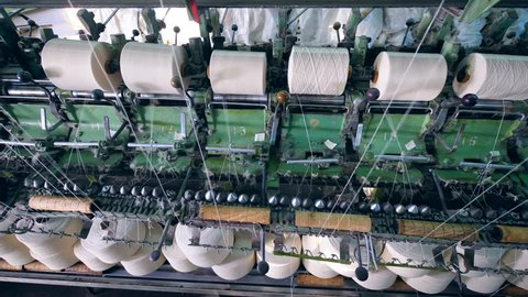 Textile factory equipment spools threads onto bobbins.