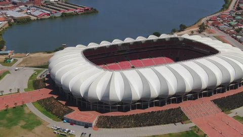 Port Elizabeth, South Africa - circa 2010s: Nelson Mandela Bay Stadium from above, turning around to see the surrounding grass park area with lake and palm trees