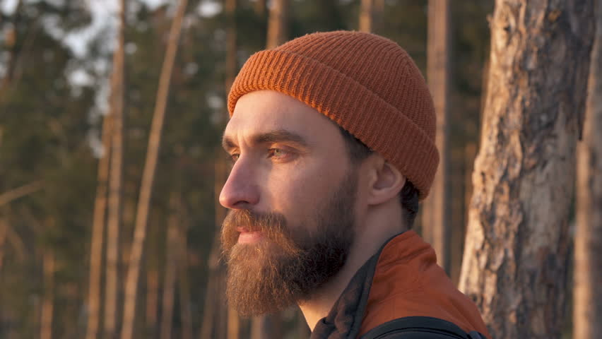 Portrait of beard man with backpack outdoors. Enjoying life and landscape.