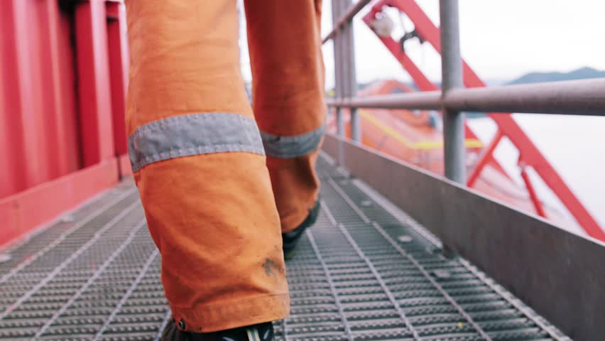 Offshore oil worker walking on oil platform. | Shutterstock HD Video #1028170046