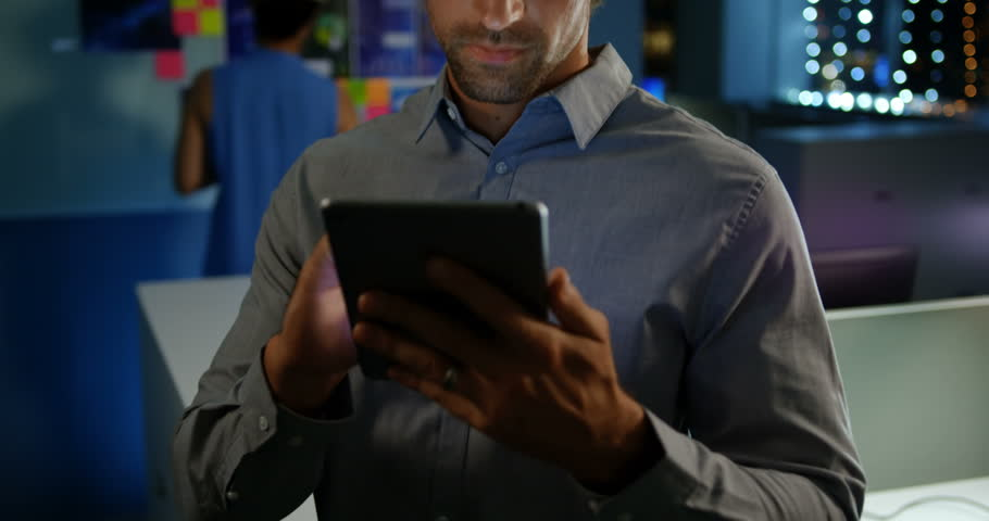 Front view close up of happy young Caucasian man executive working on digital tablet in modern office. He is looking at camera
