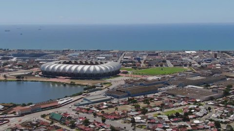 Port Elizabeth, South Africa - circa 2010: Aerial view of Nelson Mandela Bay Stadium by lake and the Indian Ocean. Surrounding roads, traffic, industrial buildings and distant ships at sea.