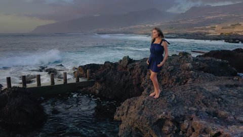 a Farewell look with Love to the Distance, a Beautiful Girl stands on the Rocks by the Ocean and looks at the Bright Sunset on a Warm Evening.Drone shot 4K. Flying Around of Young Woman on Rocky Island