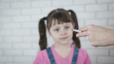 A kid is offered a cigarette. Little girl against cigarettes.