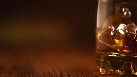 Whiskey with ice. Glass of Scotch, Irish Whisky on wooden table over brown background. Rum alcohol close-up. Glass and bottle of spirits close-up. Dolly shot. 4K UHD video slow motion