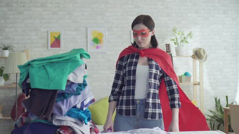 Portrait of a woman housewife superhero with the iron in hand next to an Ironing board