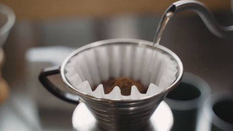 Slow motion kettle pouring hot water over freshly ground coffee beans in filter paper
