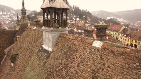 A dolly drone shot, capturing the rooftop of a vintage architechture in the city of Sighisoara on an afternoon with a community flag hoisted beside and a cityscape in the background